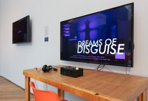 A flat screen TV showing a game called 'dreams of disguise', with controls for the game on a table.