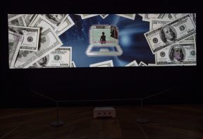 A wide screen projection of a moving image artwork showing a figure on a laptop screen, surrounded by dollar bills.