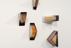 Sculptures of sandwiches encased in resin, mounted on a wall in a gallery space.