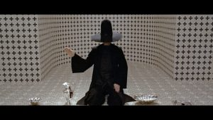 Still from Alejandro Jodorowsky's movie The Holy Mountain showing a man in black clothing