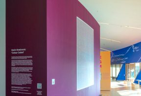 A gallery space showing a wall that has vinyl lettering reading 'Kevin Howbrook: Colour Coded'