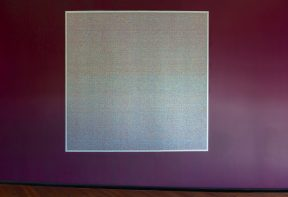 A square printed artwork on a burgundy wall showing a pixelated pattern.