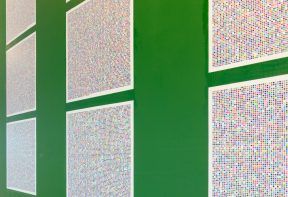 Large square printed artworks on a green wall showing a pixelated pattern.