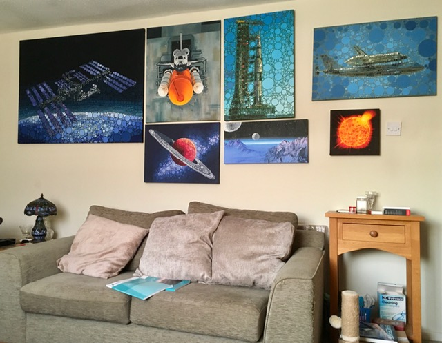 Living room with paintings of aerospace and astronomy on the walls.