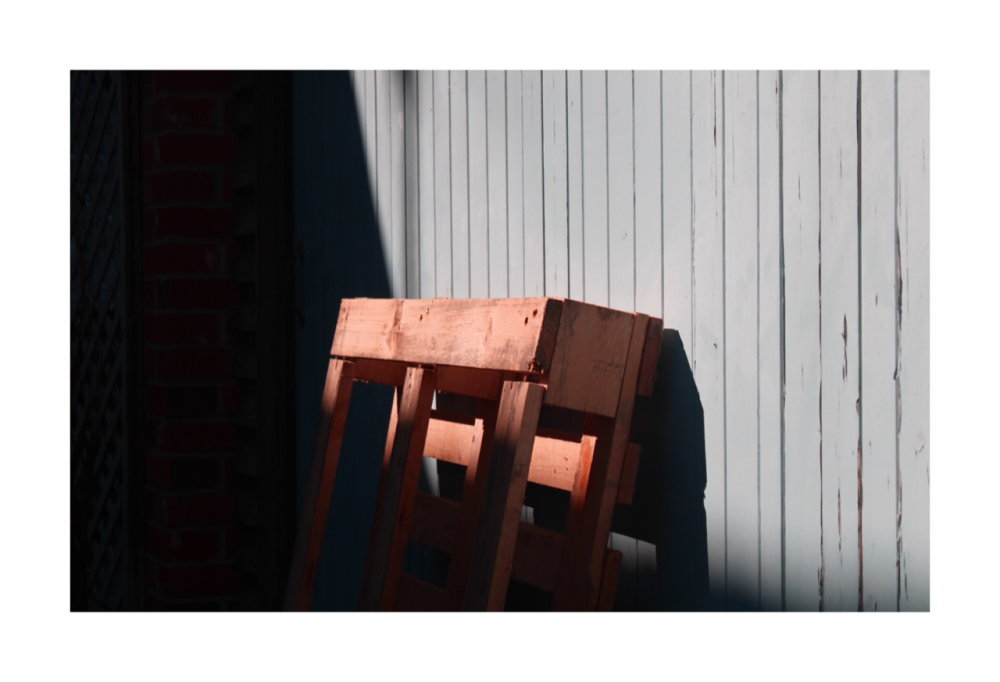 A close up of a pallet cleaning against a wall outside, half covered in shadow, the top half drenched with sunlight.