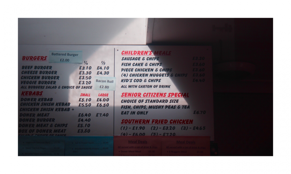 A chip shop menu covered in shadows of different shapes