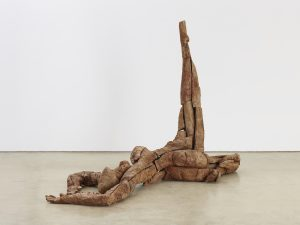 An abstract sculpture of a woman laying on the floor, with one leg raised above her.