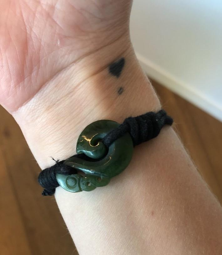 a wrist with a jade maori bracelet