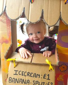 toddler playing in a homemade ice cream shop made from a cardboard box