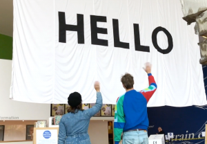 artists Iris and Tom waving at a giant flag that reads 'hello' in Firstsite's welcome area