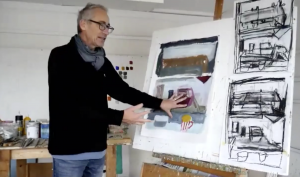 artist Simon Carter in his studio, gesturing towards a painting on an easel