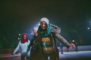 Photo of a cheerful friends learning how to ice-skate on an ice rink