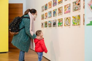 parent with their hands on their child's shoulders standing and looking at artworks in our gallery