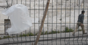 a white plastic bag caught on a wire fence
