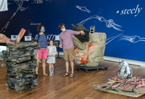 family of 4 standing amongst large scale sculptures in Firstsite's welcome area