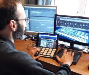 musician working at a desk with computers and music making equipment