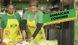 two women prepare Jamaican food in the S&S café kitchen