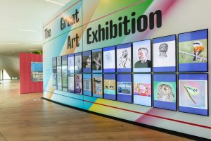 Rows of digital screens showing artworks along a colourful wall.
